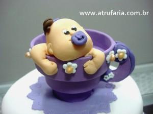 Bebezinha em pasta americana na xícara de chocolate lilás