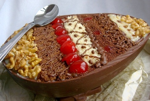 Casca de chocolate ao leite com camadas de bolo de chocolate e bolo branco, com camadas de  trufa tradicional e trufa de nozes, decorado com pedaços de nozes de cerejas